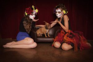 Day of The Dead girls in costume and make up blowing kisses to Chiweenie dog Dachshund mix with Chihuahua by thevetscare.com