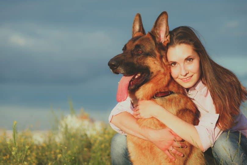Young woman hugging a German shepherd