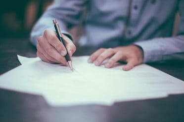 a person holding a pen, signing a document or making a contract