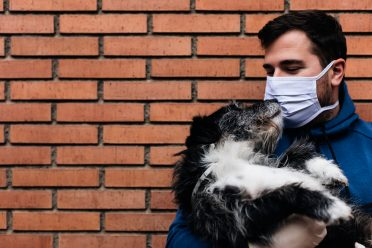 A man not letting his dog kiss him directly by wearing a mask to be safe during the Coronavirus pandemic